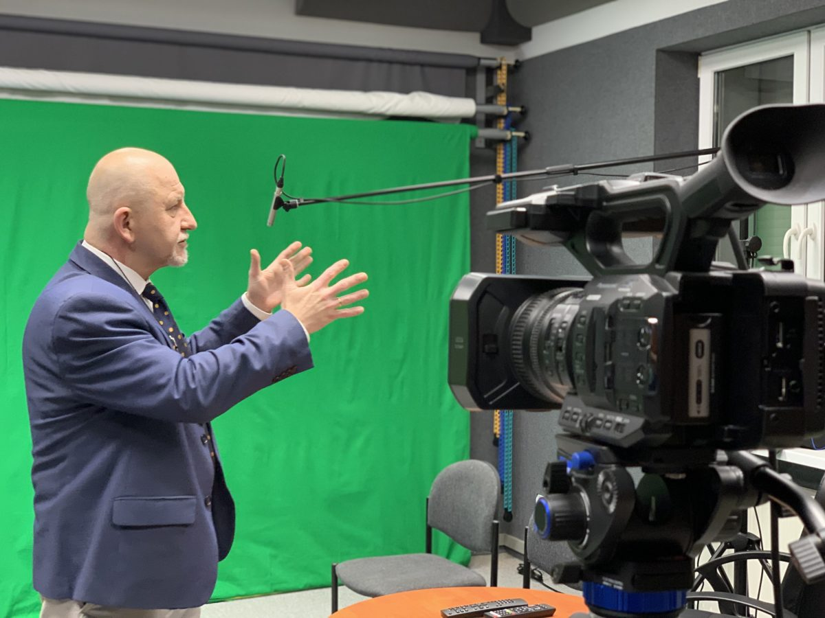 Jarosław Wujkowski, szef kaliskiego ODN-u na zielonym tle w pomieszczeniu realizatorskim. Na pierwszym planie kamera telewizyjna.