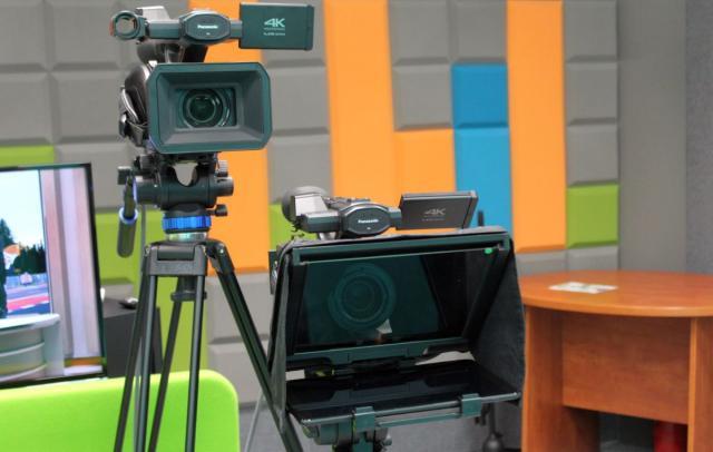 Kamera telewizyjna oraz prompter. W tle ściana z mozaiką wygłuszającą.