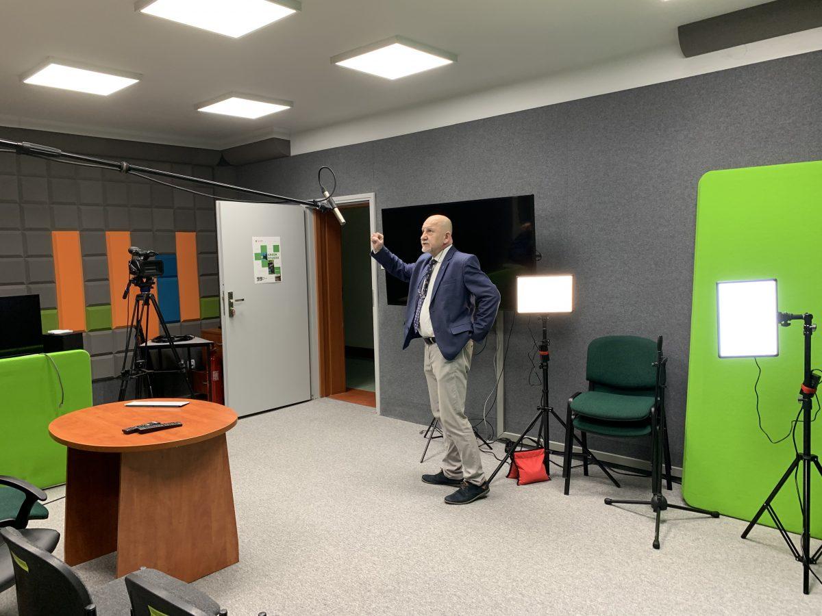 Jarosław Wujkowski, szef kaliskiego ODN-u w pomieszczeniu realizatorskim, w tle lampy LED oraz ekran. Nad Jarosławem Wujkowskim mikrofon.