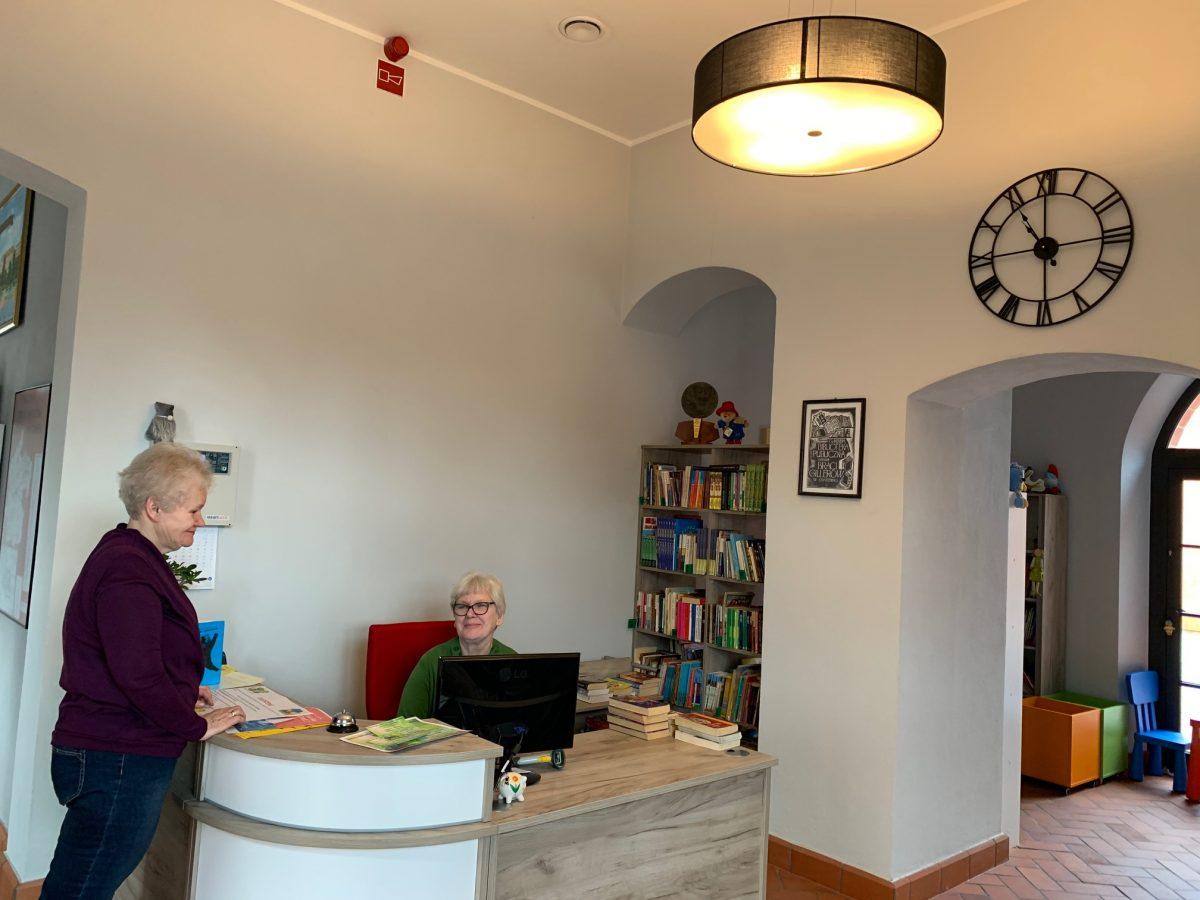 Wnętrze biblioteki w Opatówku. Widok na pulpit i stanowisko obsługi czytelnika. W tle zegar na ścianie oraz półka z książkami.