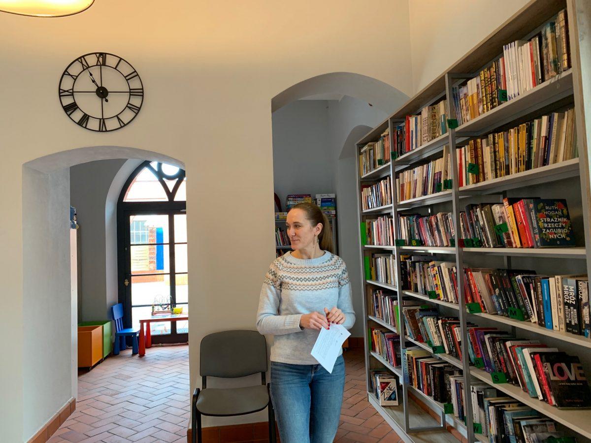 Wnętrze biblioteki w Opatówku. Widok na półki z książkami. W tle zegar na ścianie.