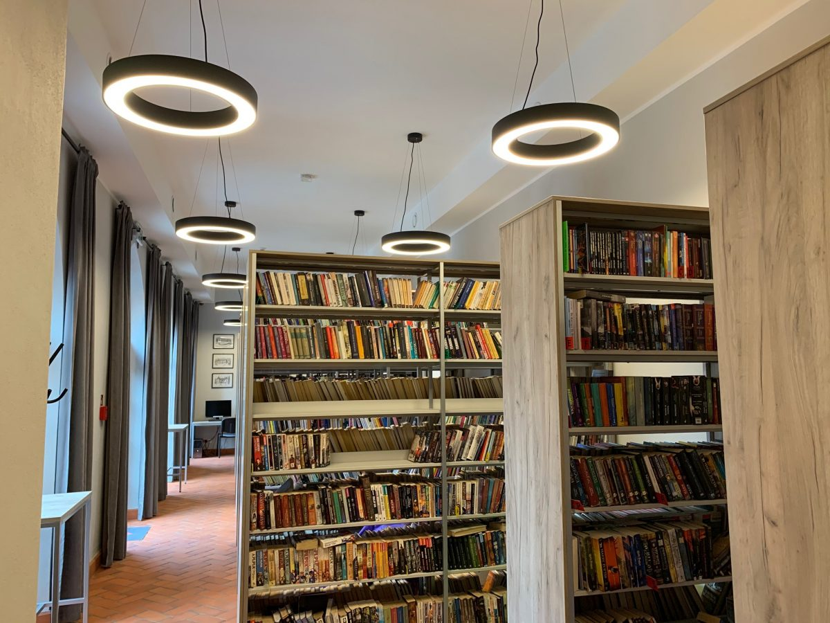 Wnętrze biblioteki w Opatówku. Widok na półki z książkami. Widoczne okrągłe elementy oświetlenia zamocowana na suficie.