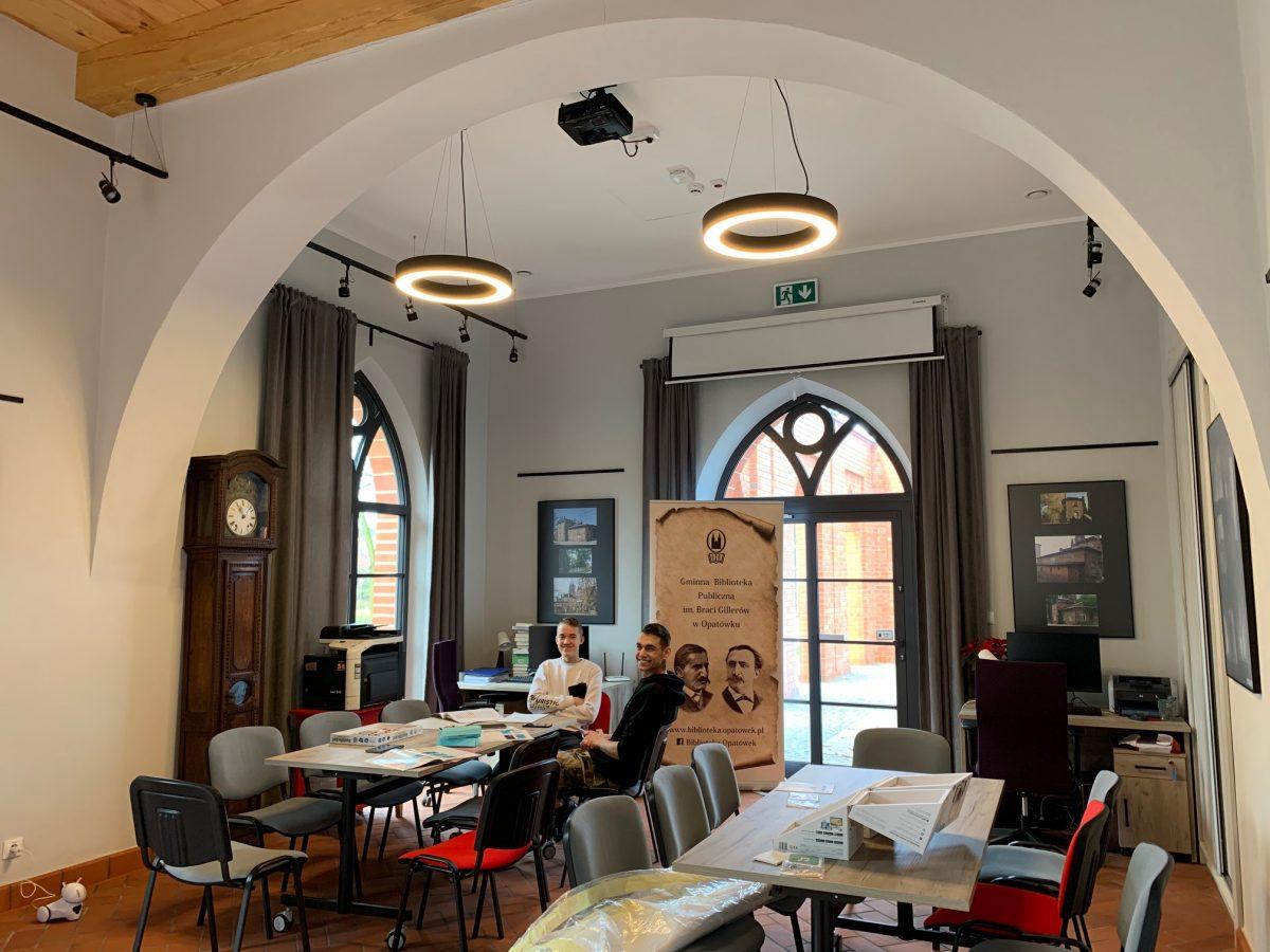 Wnętrze biblioteki w Opatówku. Widok na czytelnie wraz ze stołami i krzesłami. W tle charakterystyczne otwory okienne w stylu gotyckim.