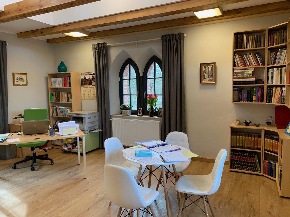 Wnętrze biblioteki w Opatówku. Widok na czytelnie wraz ze okrągły stół z krzesłami. W tle charakterystyczne otwory okienne w stylu gotyckim. Po lewej, w oddali, biurko z fotelem.