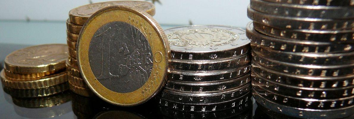 Monety Euro poukładane w stosy. Na pierwszym planie moneta 1 Euro stojąca frontem do odbiorcy.